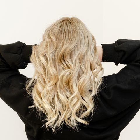 Frau mit gewellten und abmattierten blonden Haaren
