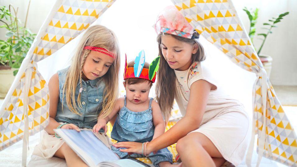 Drei Mädchen spielen Indianer