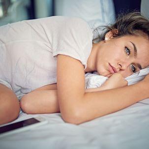 Junge Frau unglücklich im Bett