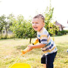 Junge mit Wasserpistole spielt im Garten