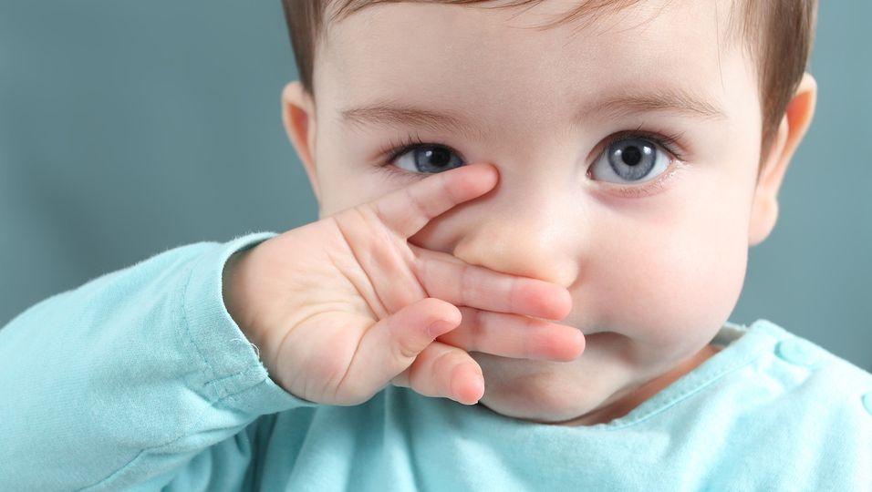 Kleines Kind fasst sich mit der Hand ins Gesicht