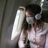 Frau im Flugzeug mit Maske und Kopfhörern