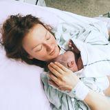 Mutter hält ihr Baby nach der Geburt im Krankenhaus im Arm