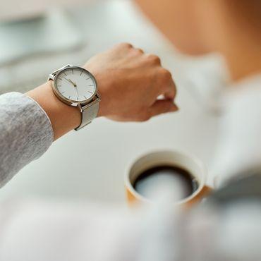 Frau, die auf eine Armbanduhr an ihrem Handgelenk schaut