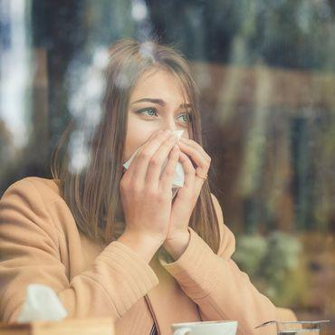 Frau hinter einem Fenster, die sich die Nase putzt