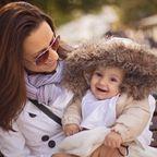 Glückliche Mutter und Baby mit Fellmütze im Freien
