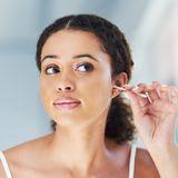 Frau reinigt sich mit Wattestäbchen die Ohren.