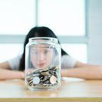 Geld anlegen, Kleingeld, Frau starrt auf Glas, Vermögen, Altersvorsorge