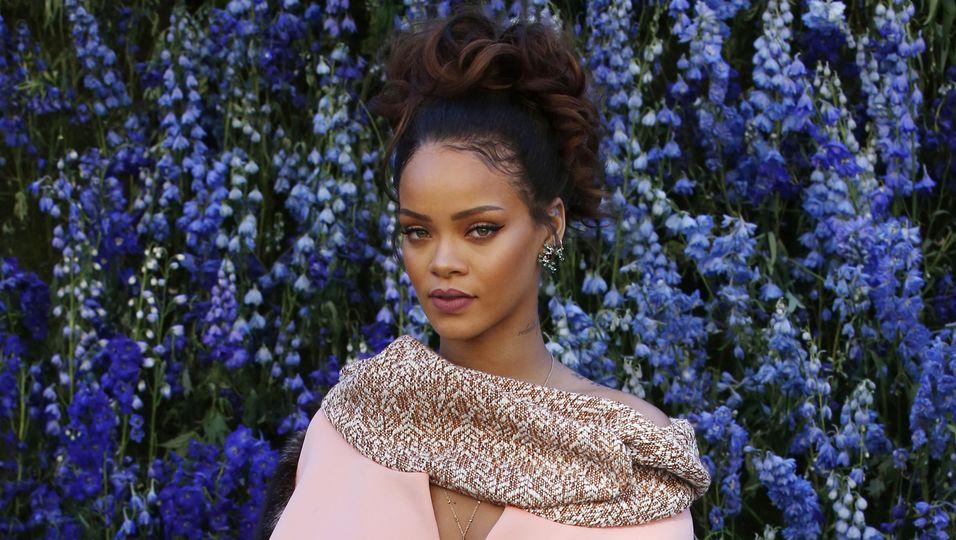 Rihanna in einem rosafarbenen Mantel.