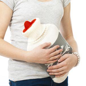Frau mit Wärmflasche gegen Bauchschmerzen