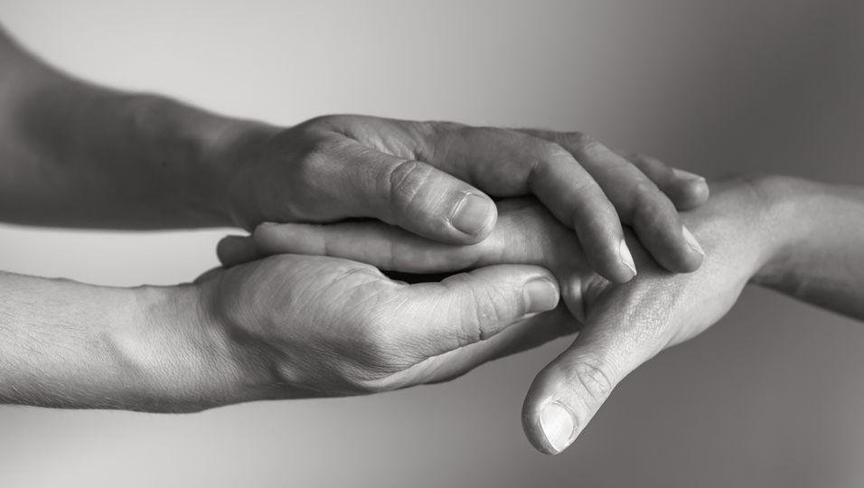 Trauernde halten Hände