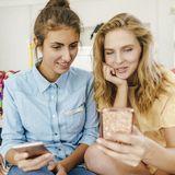 Zwei Frauen shoppen online über ihre Handys.
