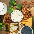 Milchprodukte, Nüsse, Gemüse und Fisch, die auf einer Holzplatte angerichtet sind.