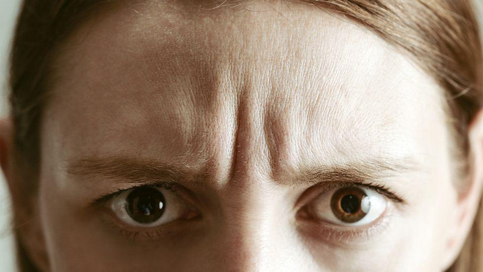 Frau legt Stirn in Falten