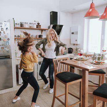 Mutter und Tochter tanzen in der Küche