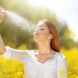 Frau verwendet Gesichtsspray in sommerlicher Natur