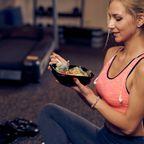 Frau isst beim Training