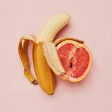 Halb geschälte Banane und Hälfte einer Grapefruit auf einem pinken Untergrund.