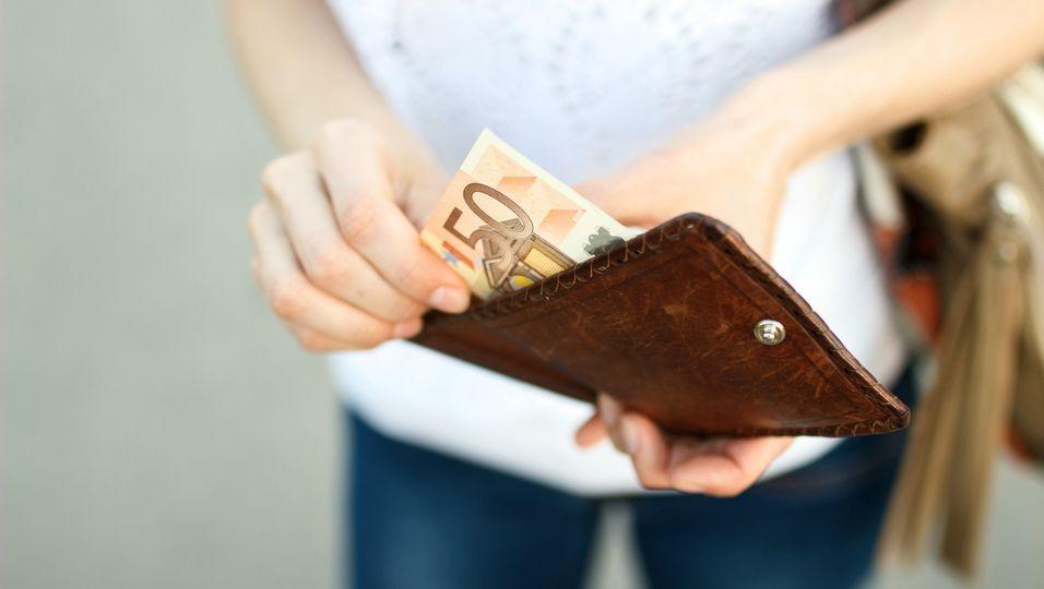Mädchen nimmt Geld aus Portemonnaie