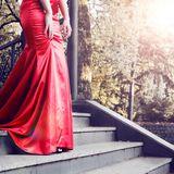 Frau in rotem Kleid auf einer Treppe