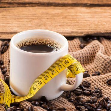 Tasse Kaffee mit Bohnen und Maßband