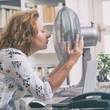Frau kühlt ihr Gesicht vor einem Ventilator