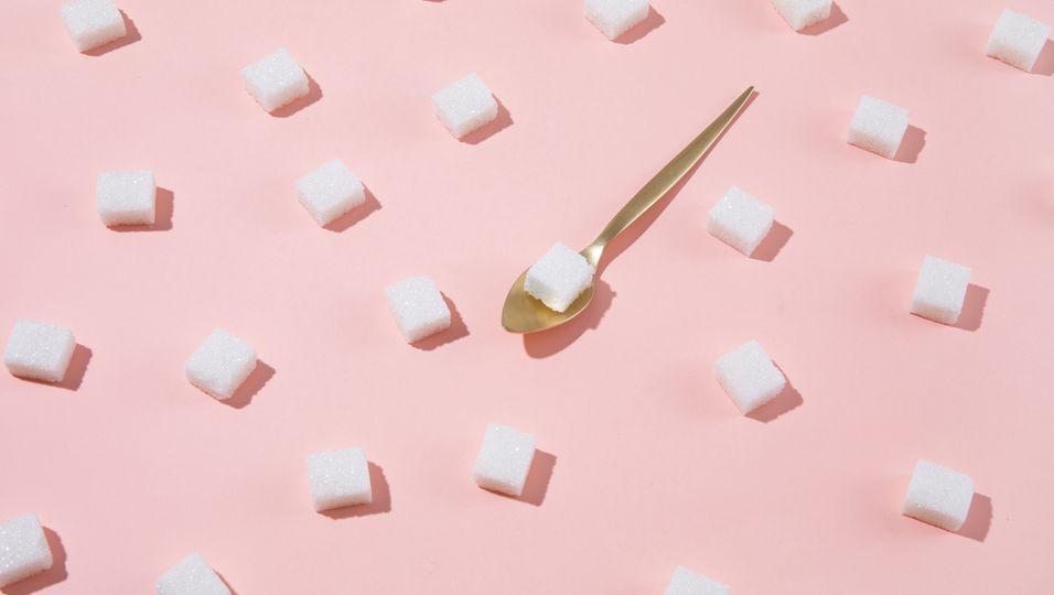 Zuckerwürfel und goldener Löffel auf einem rosa Untergrund