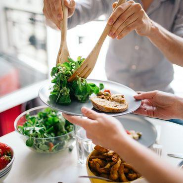 Frau, die Salat auf einen Teller legt