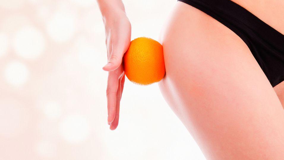 Frau hält Orange am Oberschenkel - Ausschnitt