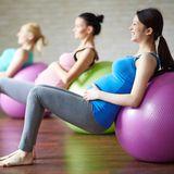 Schwangere Frauen machen Übungen mit einem weichen Gymnastikball